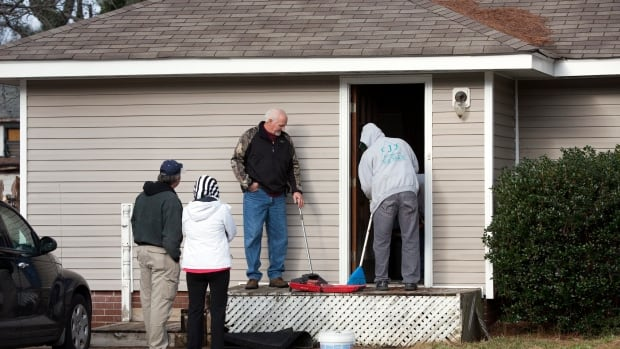 People clean the side door at a house in Chesapeake, Va., on Thursday — one of two homes connected to an apparent murder-suicide that left six members of one family dead.