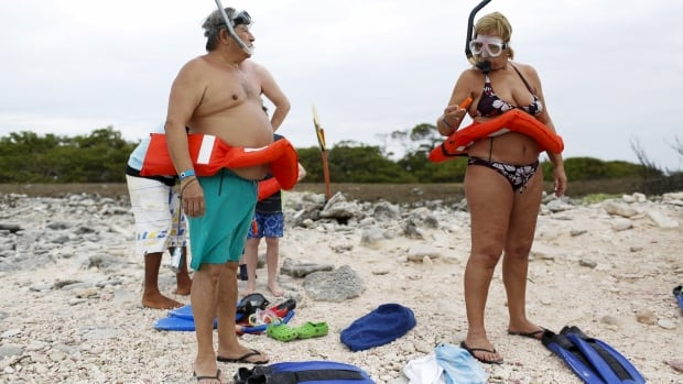 Tourists in Venezuela check their equipment before entering the water during a snorkelling class last May 29. Venezuela is one of many countries in South and Central America facing a Zika virus outbreak.