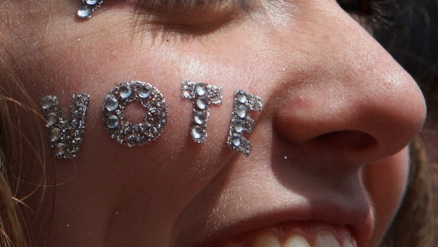 """Miss Teen London, Kelsey Johnson, 18, wears a message on her cheek at a pre-election gathering in London, Ont. April 30, 2011. About 1,000 people showed up for a """"Vote Mob"""" to encourage voters, especially the young people, to exercise their right to vote in the federal election that year."""