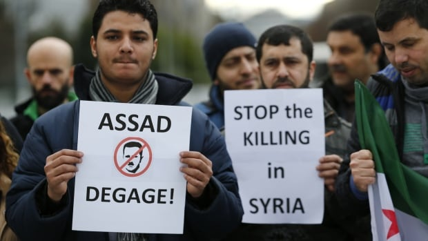 "People demonstrate against the Syrian regime ahead of the start of the Syrian Peace talks outside the UN European headquarters in Geneva. One banner reads: ""Assad go away."""
