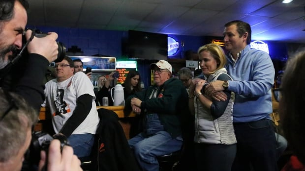 Photographers take pictures of Republican presidential candidate Ted Cruz as he hugs his wife, Heidi Cruz, moments before the Texas senator was introduced to speak at 3 Generations Bar & Grill in Ringsted, Iowa, on Friday.