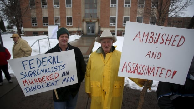 Clint Siegner, left, and his father Monte Siegner join other demonstrators during a protest outside the Harney County Court House in Burns, Ore., on Friday.  Four armed anti-government protesters are holding their ground at a remote U.S. wildlife refuge in Oregon on Saturday, two days after the FBI released a video of the fatal shooting of one of the group's spokesmen during a traffic stop.