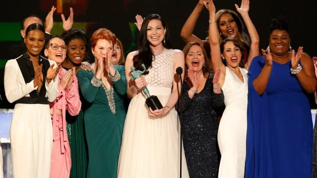 """Actress Laura Prepon, centre, accepts the award for Outstanding Performance by an Ensemble in a Comedy Series for Orange is the New Black at the 22nd Screen Actors Guild Awards in Los Angeles, California January 30, 2016. """"This is what we talk about when we talk about diversity,"""" she said of the show's cast."""