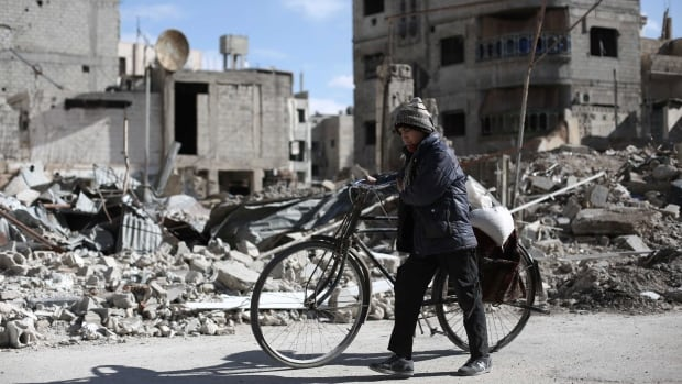 A Syrian boy walks with his bicycle past destroyed buildings in the rebel-held town of Douma, on the eastern edges of Damascus, on Jan. 24.  Sunday's explosions took place in a southern district of the city.