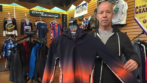 Peter Wills holds a completed jacket made for the Denver Broncos cheerleaders.