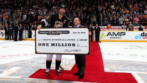 John Scott poses with the Pacific team's $1 million US cheque and NHL commissioner Gary Bettman after the 2016 NHL All-Star Game.