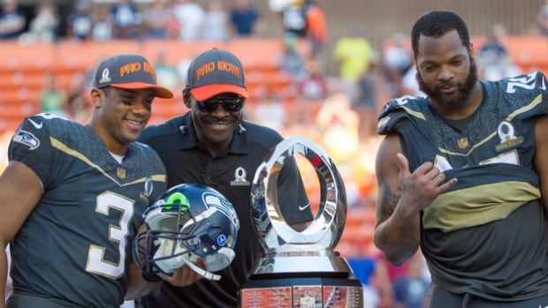 Michael Irvin, centre, takes a photo with Seattle Seahawks quarterback Russell Wilson (3), who was named the offensive player of the game, and defensive end Michael Bennett after the NFL Pro Bowl.
