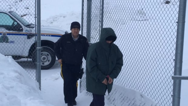 Jeffrey Salomonie, right, enters the Nunavut Court of Justice in Iqaluit. The 48-year-old Cape Dorset man is charged with first degree murder in the 2009 death of Daisy Curley.