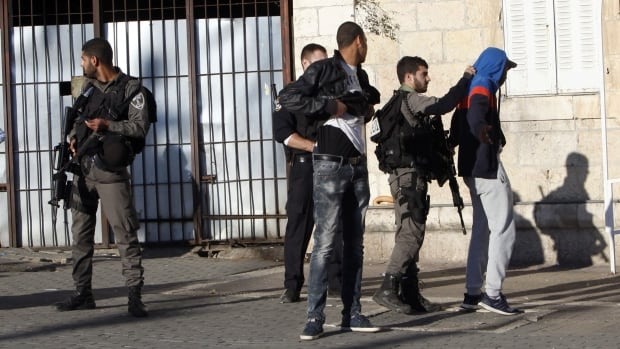 An Israeli police officer stands guard as others check a Palestinian near the scene of a shooting attack near the Damascus gate, Jerusalem's Old City, on Wednesday. Three Palestinians carrying automatic weapons, explosive devices and knives shot and stabbed two Israeli security officers in Jerusalem on Wednesday before police shot and killed the attackers, police said.