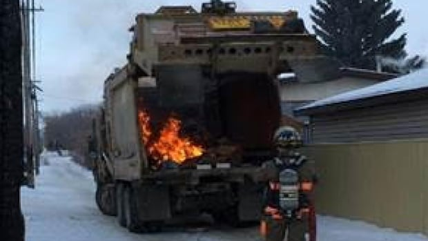 A Saskatoon firefighter sprays water on a flaming garbage truck.
