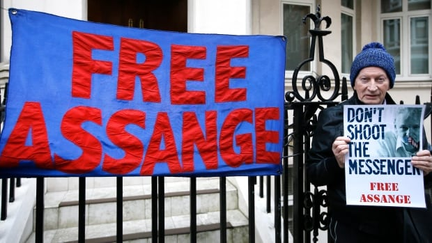 A demonstrator holds a banner outside the Ecuadorean Embassy in London, where Wikileaks founder Julian Assange is staying, on Thursday, Feb. 4, 2016.