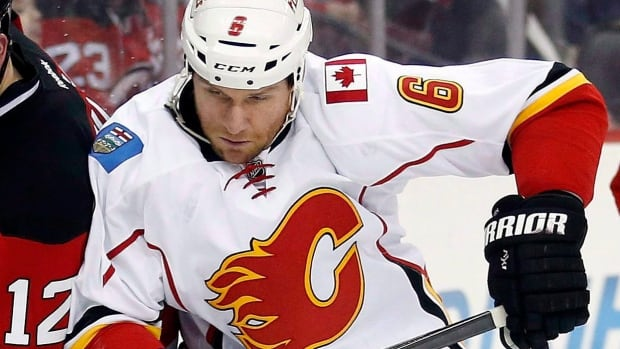 New Jersey Devils centre Reid Boucher, left, competes for the puck with Calgary Flames defenceman Dennis Wideman (6) during the second period of an NHL game on Jan. 19, 2016, in Newark, N.J. Wideman has been suspended for 20 games by the NHL for checking linesman Don Henderson from behind and knocking him down in a subsequent game.