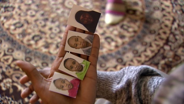 Ahmed Abdi holds photos of his wife and children