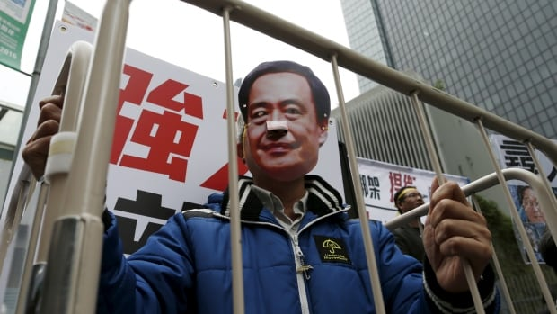 A demonstrator wears a mask depicting Causeway Bay Books shareholder Lee Bo during a protest in Hong Kong on Jan. 10.