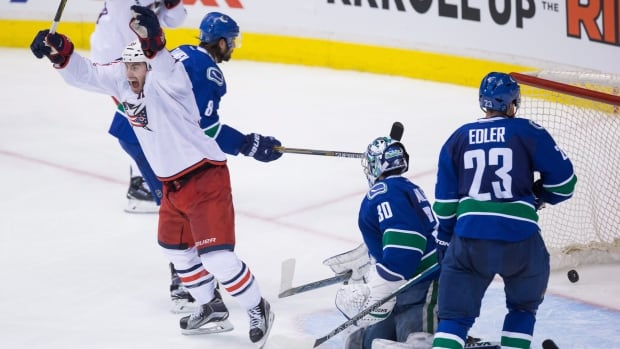 Columbus Blue Jackets' Boone Jenner, left, celebrates a goal by Scott Hartnell, in a game against the Vancouver Canucks on Thursday night.
