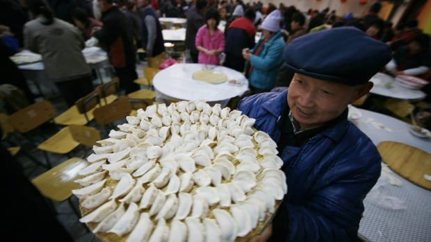 A man carries a tray of meat dumplings at a village hall in Daxing, south of Beijing, Saturday Jan. 24, 2009. Villagers gathered Saturday to make thousands of meat dumplings in preparation for a feast to celebrate Chinese New Year, which begins Monday. Dumplings are a traditional food eaten to celebrate the New Year.  (AP Photo/Greg Baker)