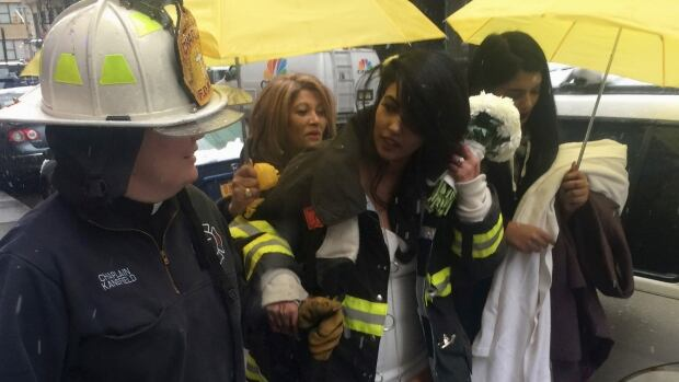 Bride-to-be Nesh Pillay, 25, is assisted by a New York City firefighter after a crane collapsed near the beauty salon where she was having her hair done in downtown Manhattan.