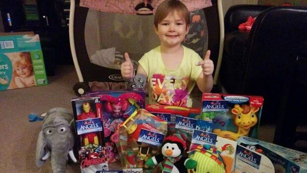 """Five-year-old Arianna Koeniger poses with her """"Angels of Hope"""" donated by friends and family."""