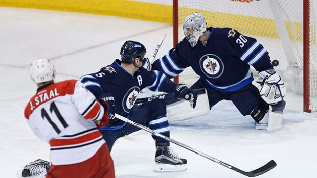 Carolina Hurricanes centre Jordan Staal scores on Winnipeg Jets goaltender Connor Hellebuyck during the first in Winnipeg on Friday.