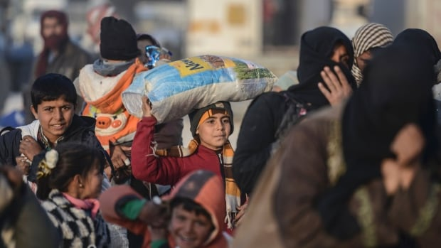 Children carry bags as Syrians fleeing the northern embattled city of Aleppo wait on Friday in Bab-Al Salama, next to the city of Azaz, northern Syria, near Turkish crossing gate.