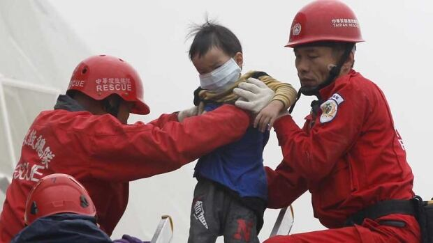 Rescue personnel help a young victim at the site where a 17-storey apartment building collapsed from an earthquake in Tainan, southern Taiwan.