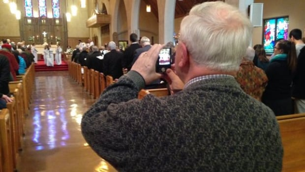 A parishioner at St. Matthias Anglican Church takes a photo during the church's final service on Feb. 7, 2016. Declining membership is forcing the parish to merge with another Anglican congregation in Ottawa.