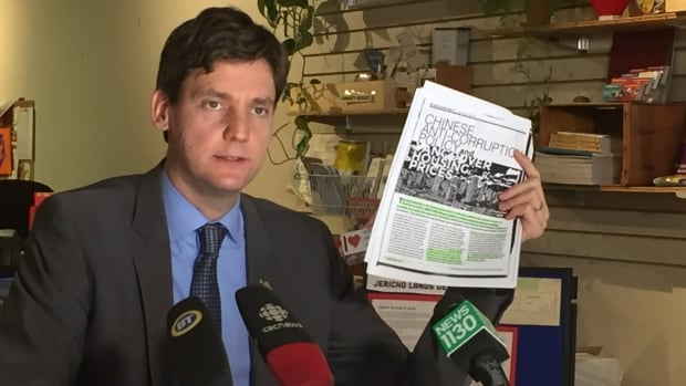 NDP housing critic David Eby holds up a copy of a real estate industry report that says financial corruption is not a problem in the Vancouver market. He believes otherwise.
