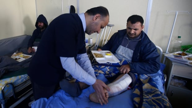 A Syrian doctor attends an injured man from Syria at a small clinic near the Turkish-Syrian border in the southeastern city of Kilis on Tuesday.