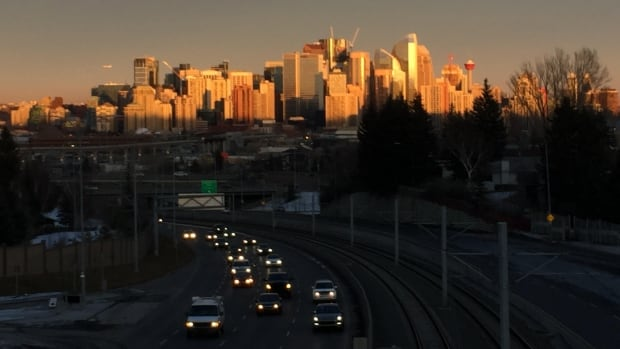 The setting sun illuminates downtown Calgary as afternoon commuters make their way home.