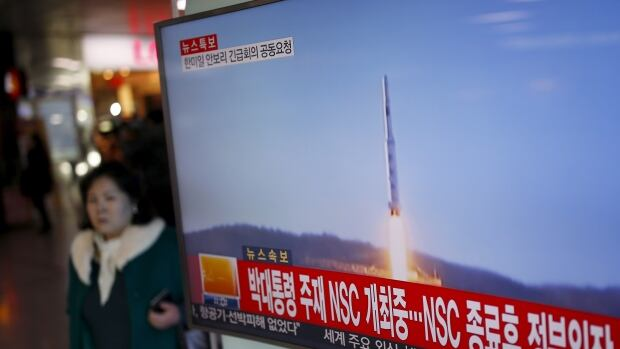 A woman walks past a TV screen broadcasting a news report on North Korea's long-range rocket launch at a railway station in Seoul, South Korea, Sunday.