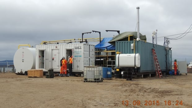 Colville Lake, N.W.T.'s new hybrid power system combines two solar arrays and a three battery storage system with diesel generators. The white structure houses the batteries, while the blue structure holds the generators.