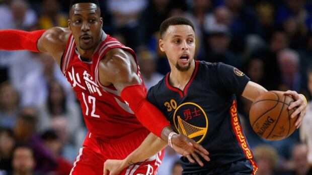 Steph Curry, right, of the Golden State Warriors, looks to get around the Rockets Dwight Howard in San Francisco. Curry poured in 35 points to lead the Warriors to their 42nd consecutive victory at home.