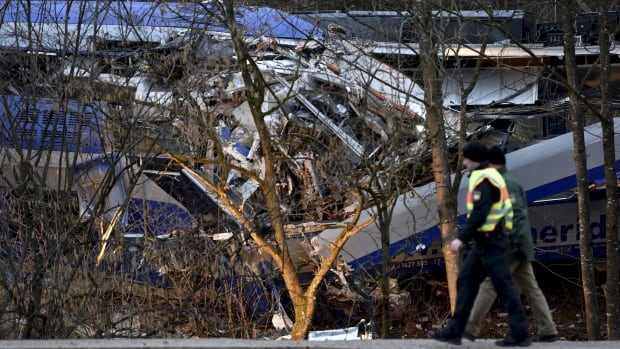 Policemen walk in front of two crashed trains near Bad Aibling in southwestern Germany early Wednesday.