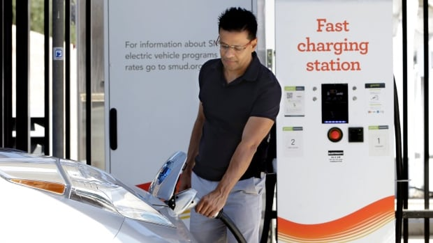 In this September 2015 photo, Darshan Brahmbhatt unplugs a charger from his electric vehicle at the Sacramento Municipal Utility District charging station in Sacramento, Calif. Ontario has become the latest jurisdiction to sweeten its incentives to encourage the adoption of electric vehicles.