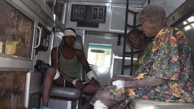 Survivors of a suicide bomb attack at a refugee camp receive treatment inside an ambulance, in Maiduguri, Nigeria on Wednesday. Two female suicide bombers blew themselves at the northeast Nigerian camp, killing dozens.