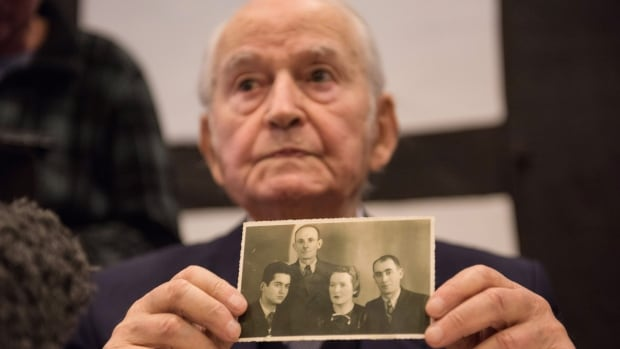 Concentration camp survivor Leon Schwarzbaum presents an old photograph showing himself, left, next to his uncle and parents who all died in Auschwitz, during a press conference in Detmold, Germany, Wednesday.