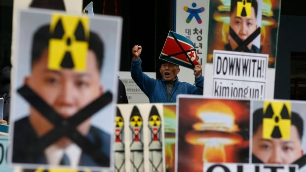 A South Korean man holding a crossed North Korean flag shouts slogans among placards with crossed portraits of North Korean leader Kim Jong-un pasted with the radiation warning symbol during an anti-North Korea rally in downtown Seoul on Thursday.
