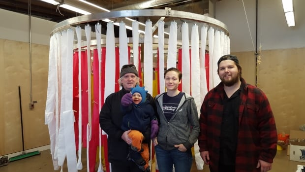 Laurentian architecture school director Terrance Galvin holds his son, Gabriel, beside students Danielle Kastelein and Matt Hunter in front of their winter installation project.