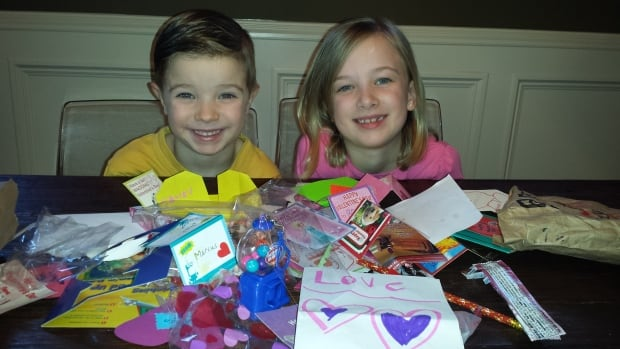 Four-year-old Ben Cedergren and seven-year-old Brooke Cedergren show off their Valentine's Day loot, including a paper airplane set, pencils and a bubble gum machine.