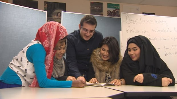 A group of refugee teenagers look at a photo album of memories from an after-school program aimed at helping refugee children deal with trauma.