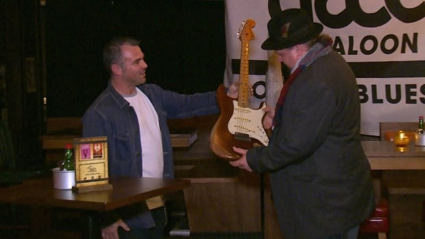 Jason Webb hands Jason Buie his long lost Fender Stratocaster Wednesday evening.