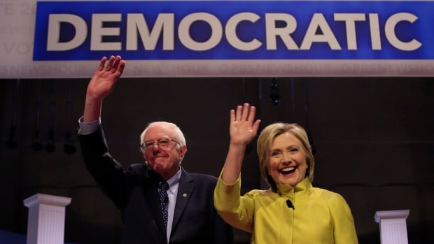 Bernie Sanders, left, and Hillary Clinton take the stage before a Democratic presidential primary debate Thursday in Milwaukee.