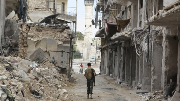A Free Syrian Army fighter carries his weapon as he walks past damaged buildings in the old city of Aleppo, Syria in August 2015.