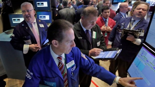 Glenn Carell, foreground, works with traders at his post on the floor of the New York Stock Exchange, on Friday. Canadian and U.S. stocks were higher, seeking their first gain this week, as beaten-down energy and financial companies rebounded.