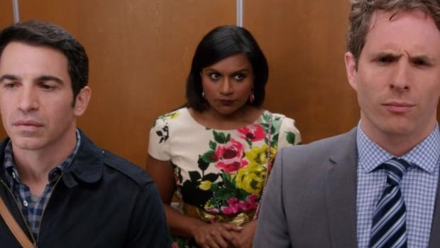 An anxious Mindy Lahiri stands in an elevator between two of her suitors, characters Danny Castellano (left) and Cliff Gilbert (right), in the Fox series The Mindy Project.