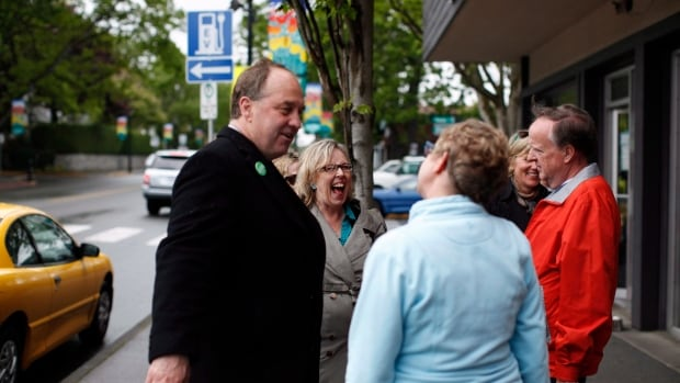 Federal Green Party leader Elizabeth May and Oak Bay/Gordon Head B.C. Green Party MLA candidate Andrew Weaver brave the elements to wave at traffic and speak to people  in Victoria Monday May 13, 2013.