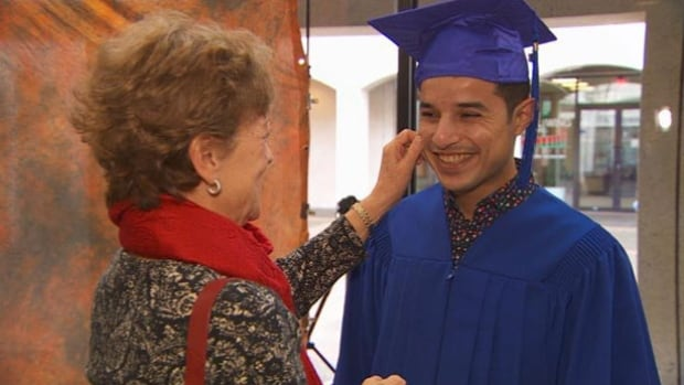 Sponsor Deana Brynildsen pinches Mohammed Al Saleh's cheek after he graduates with a medical assistant diploma from Drake Medox College.