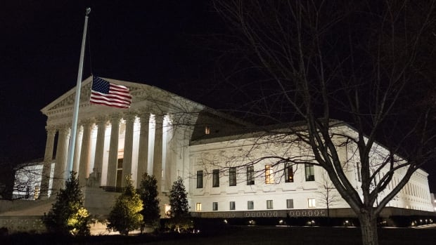 A U.S. flag flies at half-staff in front of the U.S. Supreme Court in Washington on Saturday to mark the death of Justice Antonin Scalia, 79.