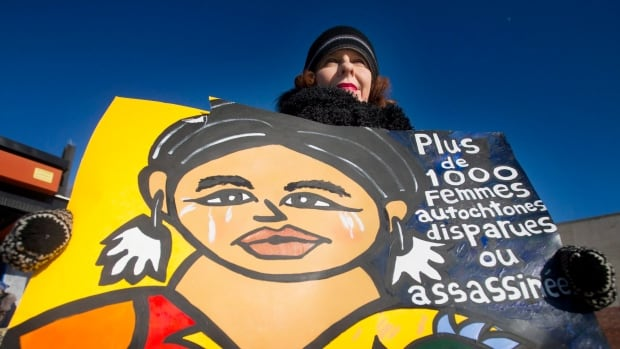 A woman holds up a sign as she participates in the 7th annual memorial march to raise awareness for the hundreds of missing and murdered aboriginal women in Montreal on Sunday, Feb. 14, 2016.