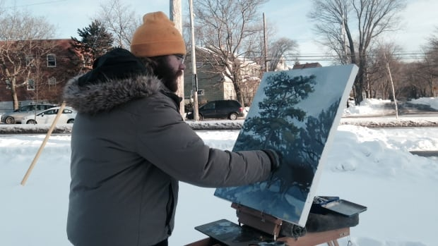 Alex King, 22, is painting in Saunders Park even though it feels like -17 with the wind chill.